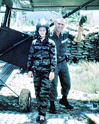 Old photo of a woman in fatigues, wearing a helmet, standing with a pilot who's tipping his hat.