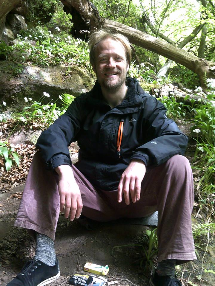 Anthony Ogley sitting on a tree stump facing the camera