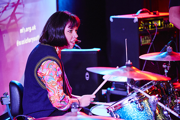 Female brown-haired drummer plays drum kit onstage