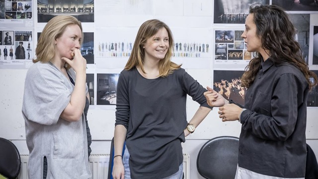 Rebecca Frecknall, a white woman with blonde shoulder-length hair stands smiling with one hand on her hip, talking in rehearsal to two other women against a background of set and costume designs on a wall.
