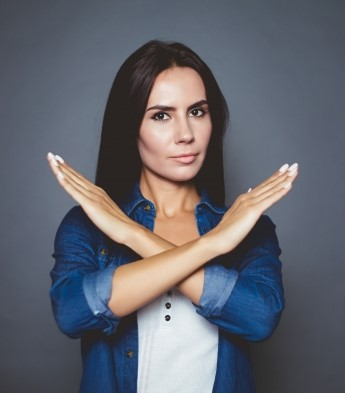 Dark haired woman with arms in the shape of an X