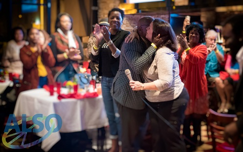 ALSO Executive Director hugging Community Ally Award Recipient and other attendees applausing in the background