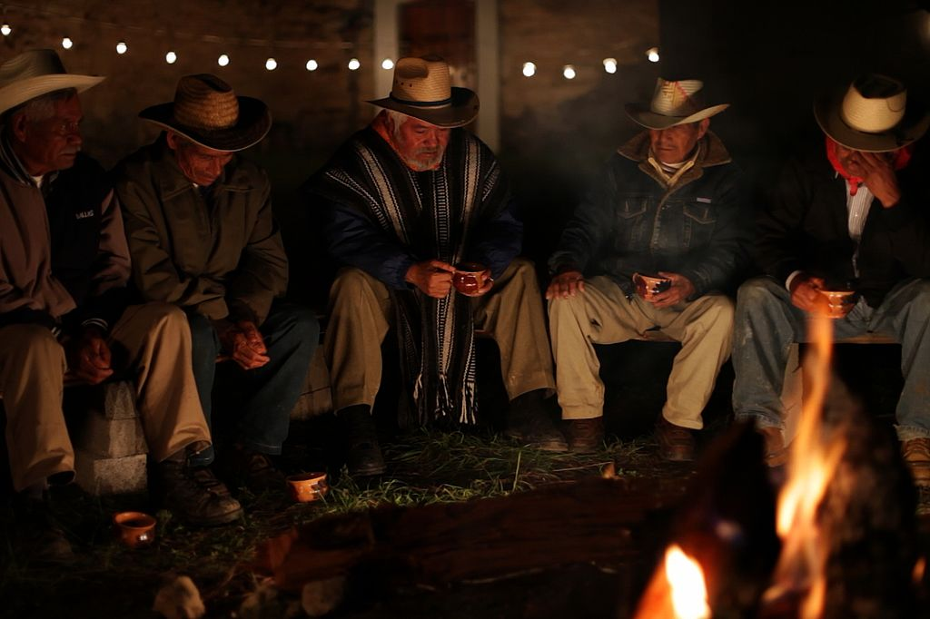 Indigenous Mexican Elders sit around a fire