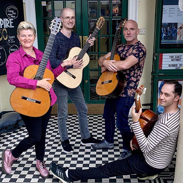 Four musicians with guitars pose in front of a theatre door