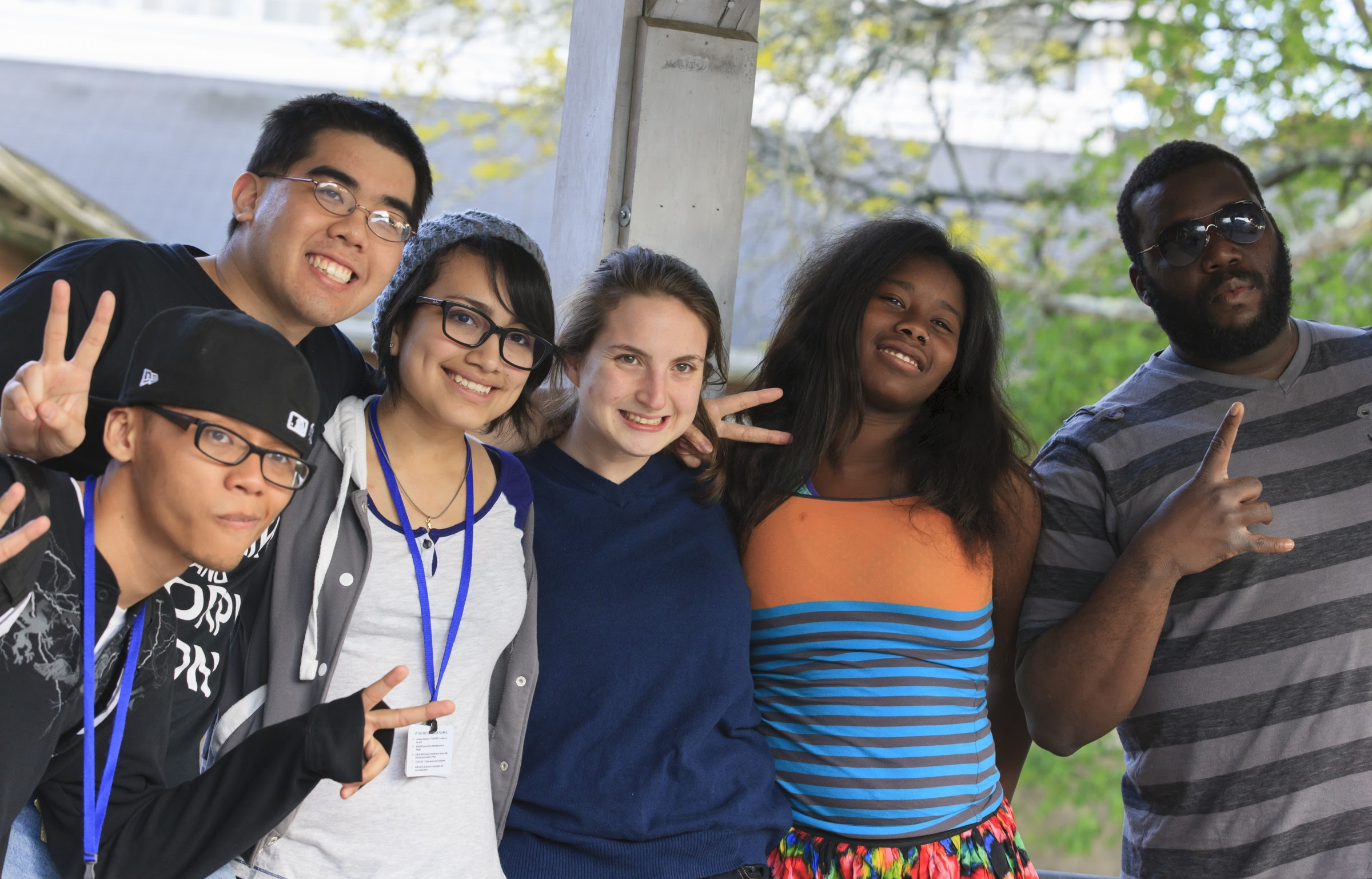 Six young people facing forward, arms interlinked, smiling and giving peace signs