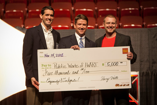 EngenuitySC Executive Director George Hutton and Wells Fargo's Holt Chetwood award the 2012 Ignite! Ideas Contest prize of $5000 to Public Works of HeArt founder Will Bryan at last year's celebration.
