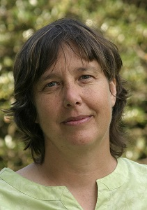 Lauren Abramson, headshot of fair skinned woman with short brown hair, wearing a light green top and standing outdoors in front of greenery