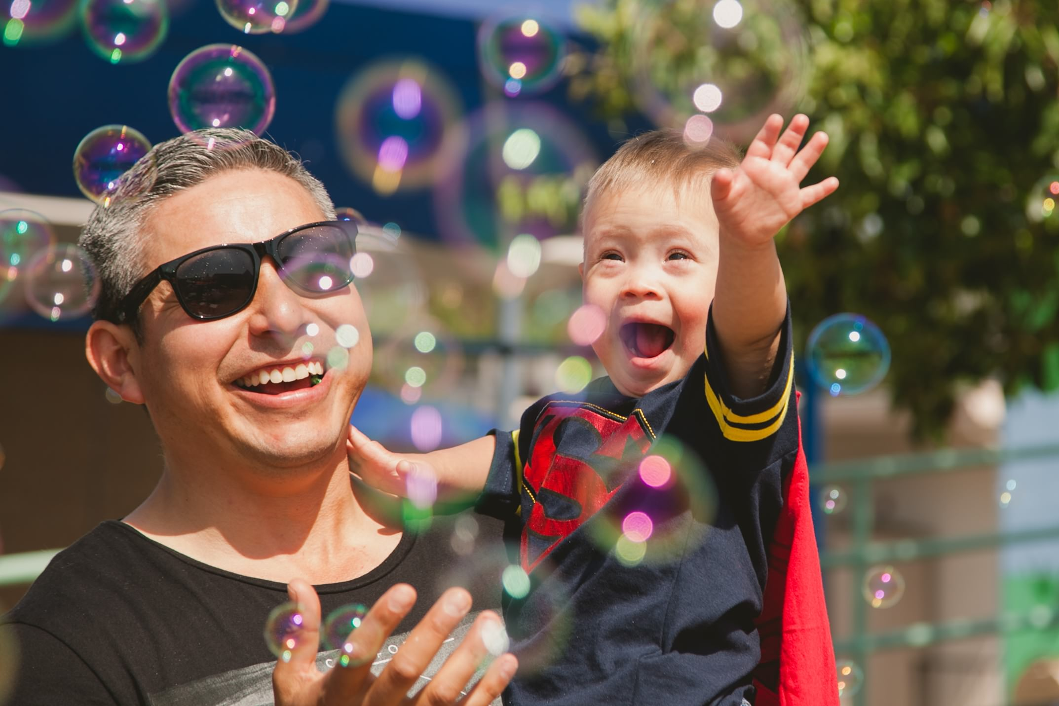 Toddler dressed as Superman enjoying bubbles with his father.