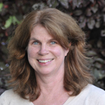 Headshot of Linda Nowlan, female, mid 40s, blue eyes, dirty blonde hair, white shirt, leaf background.