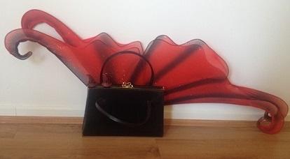 Red wings, red horns, vintage handbag as examples of costuming.