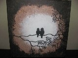 Two lovebirds sitting on a branch backlit by a bright moon