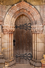Cathedral wooden door with surrounding stone