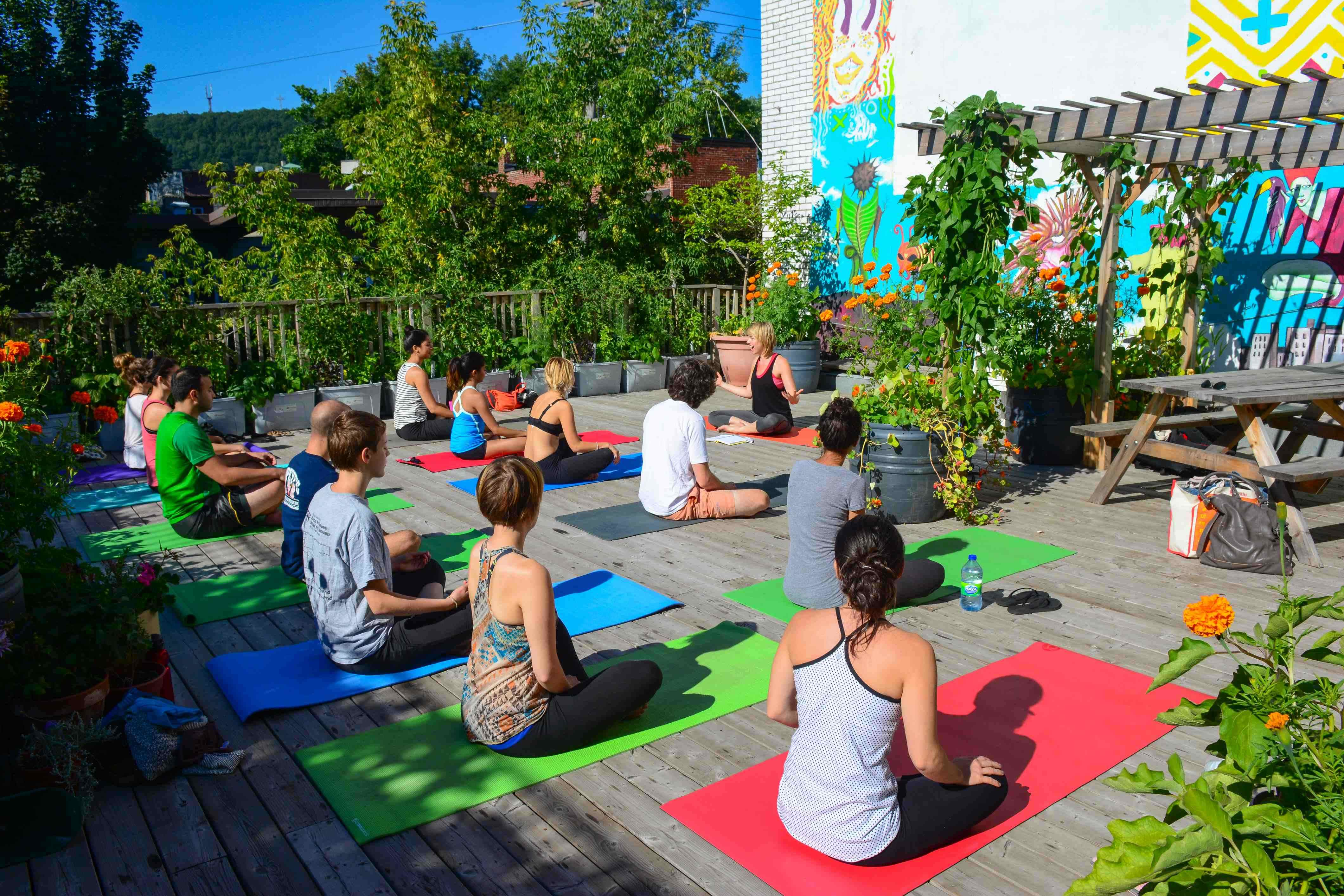 A group of yoga students step on to their yoga mats and stretch towards the sky atop the 1000-square foot urban vegetable garden which sits on rooftop of Santropol Roulant, a Montreal-based non-profit organization that builds connection between multi-generational communities through urban agriculture and meal delivery.