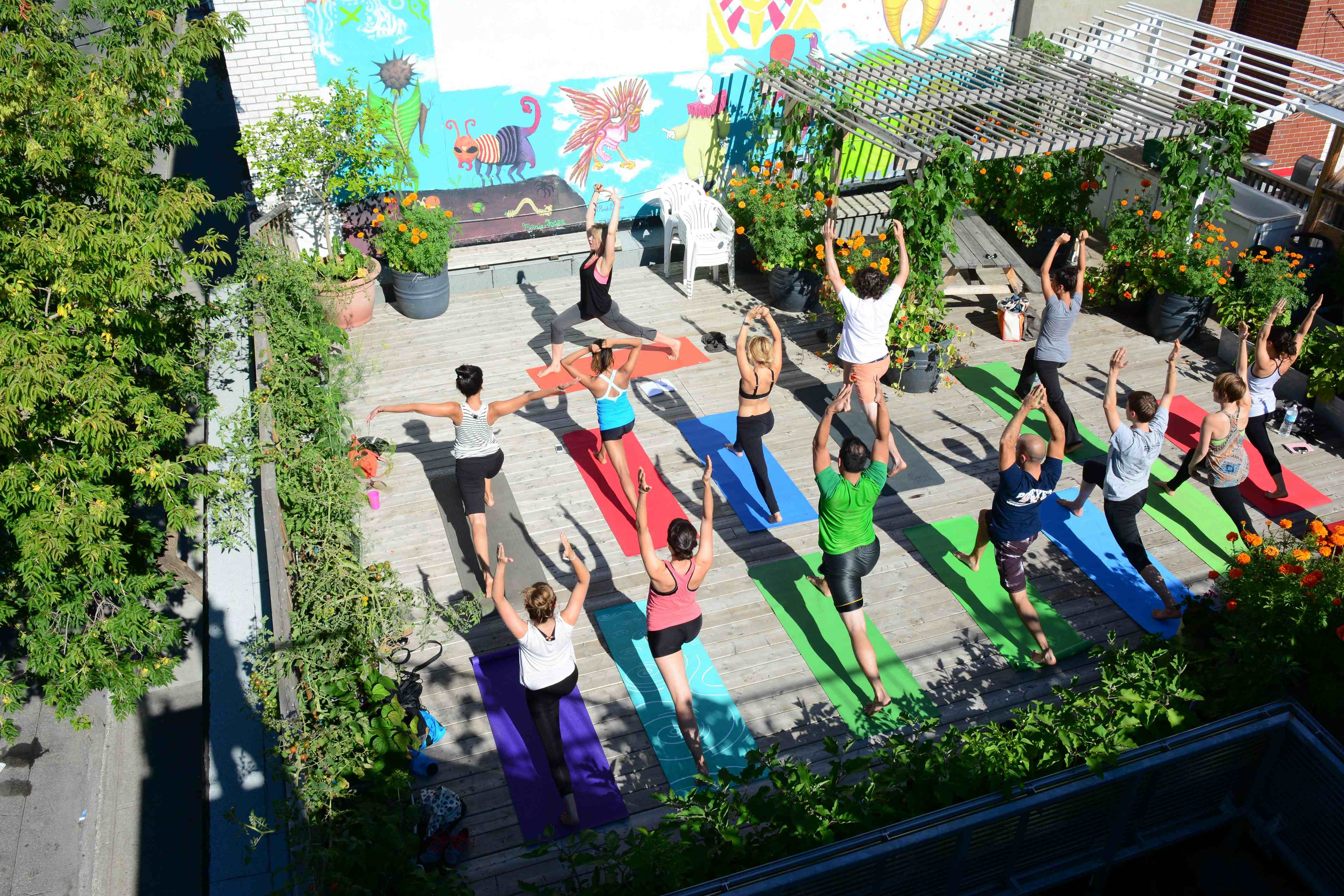 Yoga students enjoy the sun during their practice on the rooftop of Santropol Rouland in downtown Montreal