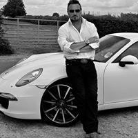 Simon Stepsys standing in frontof his White Porsche Car