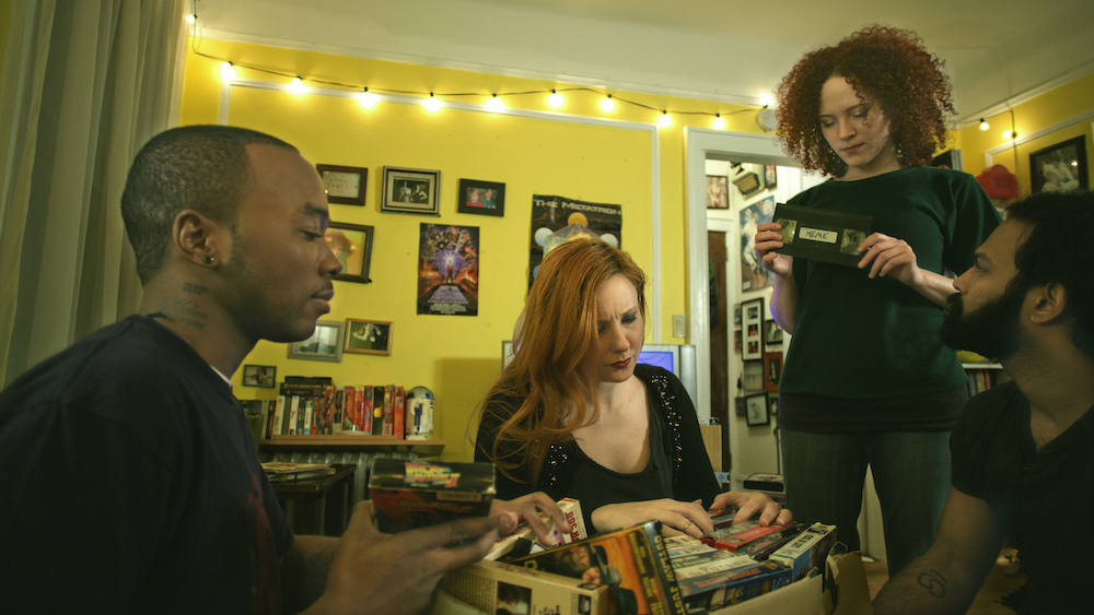 Kyle (Chaz Cleveland), Carrie (Kitty Ostapowicz), Jennifer (Sarah Schoofs), and Tommy (Shivantha Wijesinha) gathered around a box of VHS tapes. Click the image to see the trailer for the film.