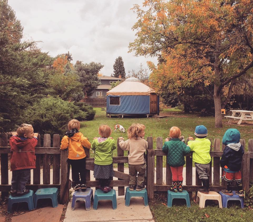 Children in fall coats looking over a fence