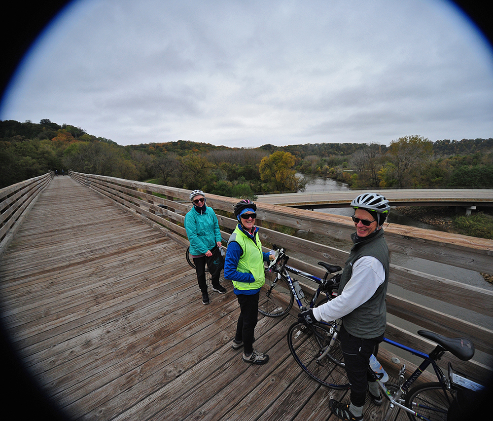 A group of bicyclists stop on a converted railroad trestle during the Mankato River Ramble Bike Tour