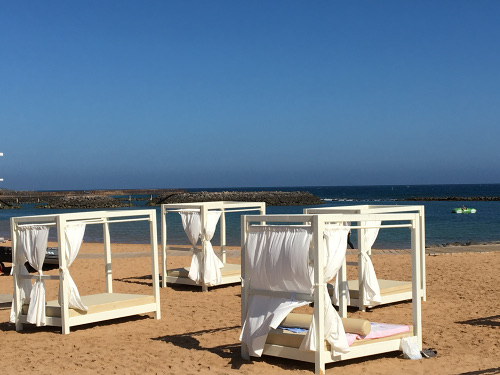 Relaxing sunbeds on the beach at Caleta