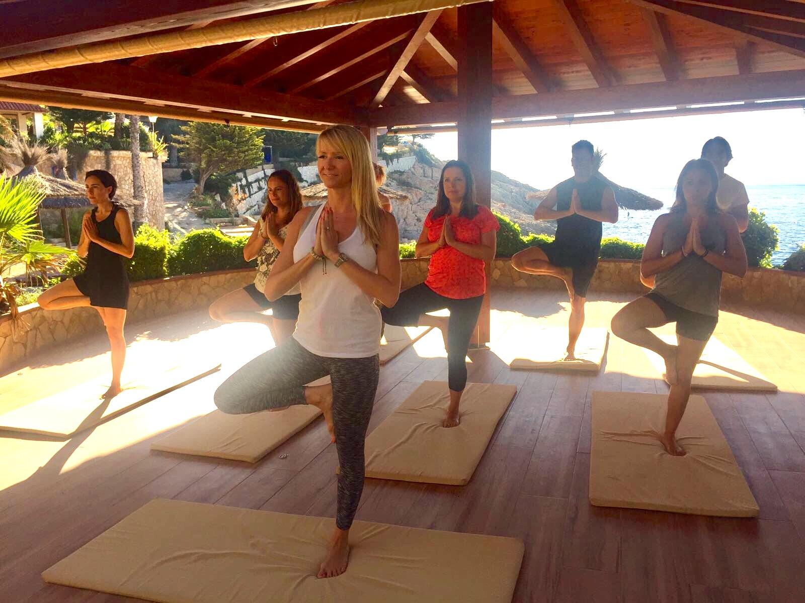 Practicando yoga en frente del mar