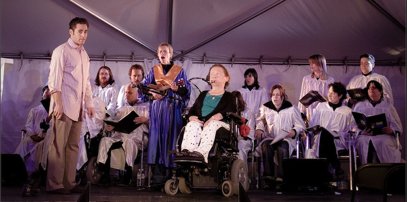 Photo of the full cast on stage in the original production with Judith Snow, Michael Rubenfeld and Alex Bulmer standing before the choir